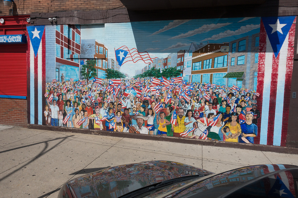 "This mural was painted as part of the 11th annual ""Fiest Boriqua"" 2004, and dedicated to Lolita Legron. ""A bead from Lolita's rosary polished by her prayers for the homeland."" Seigned and painted by Gamaliel Ramirez, Assistance by Star Padilla, Luis Ortiz, Moncho, Melissa Cintron, members of the community and the youth on the corner of Division and Campbell. This project was sponsored by Gamaliel Ramirez Studios, Near Northwest Neighhborohood Network. Batey Urbano and Arci-treasure. The mural depicts some famous people including National Puerto Rican icon Lolita Lebrón, Pedro Pietri, and Don Pedro Albizu Campos, the leader of the Puerto Rican Independence Movement who is depicted as a bronze statue on the left of the image."