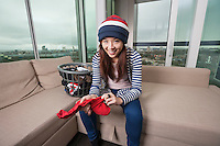 Portrait of smiling young woman doing laundry work in living room at home