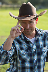 portrait of a handsome cowboy outdoors tipping his cowboy hat