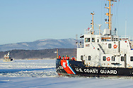 Crew members of the United States Coast Guard cutter Sturgeon Bay stand on the deck as the icebreaker approaches a pier in the Hudson River in Hudson, New York. The historic Hudson-Athens Lighthouse is at left, and the Catskill Mountains are in the background.