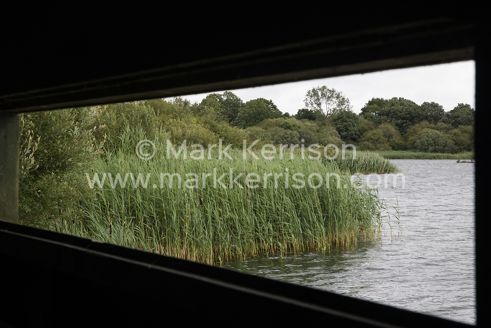 Calvert, UK. 27 July, 2020. A view across the lake from one of the bird hides at Calvert Jubilee Nature Reserve. On 22nd July, the Berks, Bucks and Oxon Wildlife Trust (BBOWT) reported that it had been informed of HS2's intention to take possession of part of Calvert Jubilee nature reserve, which is home to bittern, breeding tern and some of the UK's rarest butterflies, on 28th July to undertake unspecified clearance works in connection with the high-speed rail link.