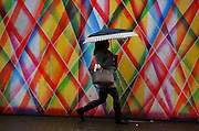 A woman walks through the rain in downtown Seattle in front of a colorful backdrop.<br />