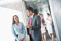 Businessman talking with female colleague while walking in office corridor
