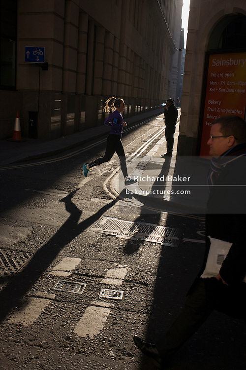 A woman jogger runs past a male exhaling smoke from his cigarette, in the City of London.
