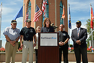East Meadow, New York, U.S. - September 3, 2014 - KATHLEEN RICE, at podium, Democratic congressional candidate (NY-04), releases a whitepaper on veterans policy and announces formation of her campaign's Veterans Advisory Committee, at Veterans Memorial at Eisenhower Park, after touring Northport VA Medical Center with outgoing Rep. CAROLYN MCCARTHY (in white jacket). Congresswoman McCarthy and 4 committee members joined Rice at the press conference: PAUL ZYDOR, (in blue shirt) of Merrick, U.S. Navy, Korean War Veteran; PAT YNGSTROM, (in black T-shirt and cap) of Merrick, U.S. Army Paratrooper, Vietnam War Veteran; STEVE BONOM, (in black T-shirt and pants) of Massapequa, U.S. Navy, Vietnam War Veteran; and JEREMIAH E. BRYANT, (wearing American Flag tie and black suit) of Rockville Centre, U.S. Army, Vietnam War Veteran. Rice is in her third term as Nassau County District Attorney, Long Island.