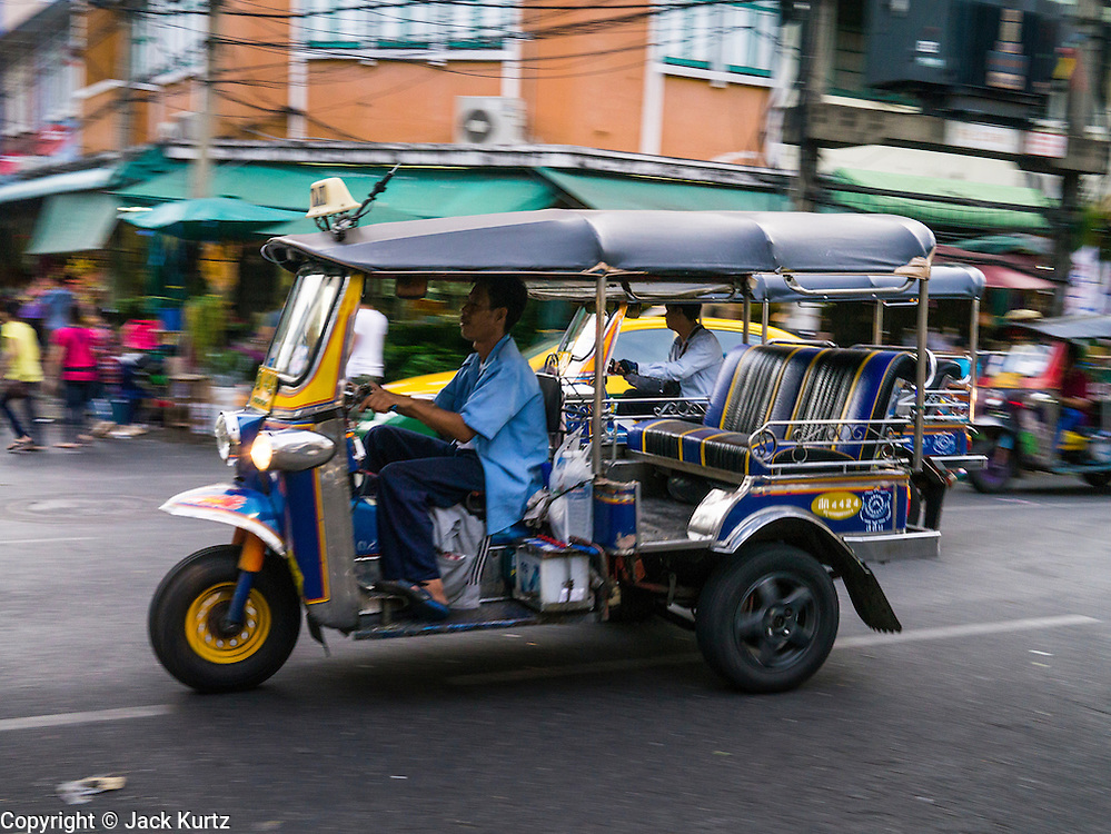 """17 MAY 2013 - BANGKOK, THAILAND:   A """"tuk-tuk,"""" or three wheeled taxi, on Chakphet Road in front of the flower market in Bangkok. The Bangkok Flower Market (Pak Klong Talad) is the biggest wholesale and retail fresh flower market in Bangkok. It is also one of the largest fresh fruit and produce markets in the city. The market is located in the old part of the city, south of Wat Po (Temple of the Reclining Buddha) and the Grand Palace.   PHOTO BY JACK KURTZ"""