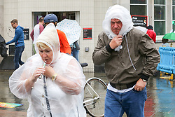 © Licensed to London News Pictures. 30/07/2019. London, UK. A couple wearing rain ponchos in Camden Market, north London during heavy rainfall. Photo credit: Dinendra Haria/LNP
