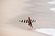 A surfer makes his way out of the water at Waimea Bay on the North Shore of Oahu.