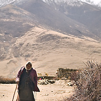An Tibetan old woman walks in the small village of Narme, one of the red spots of the Kashin-Beck Disease, in the Lhasa river valley. Tibet, China. April 14, 2007. Photo: Bernardo De Niz