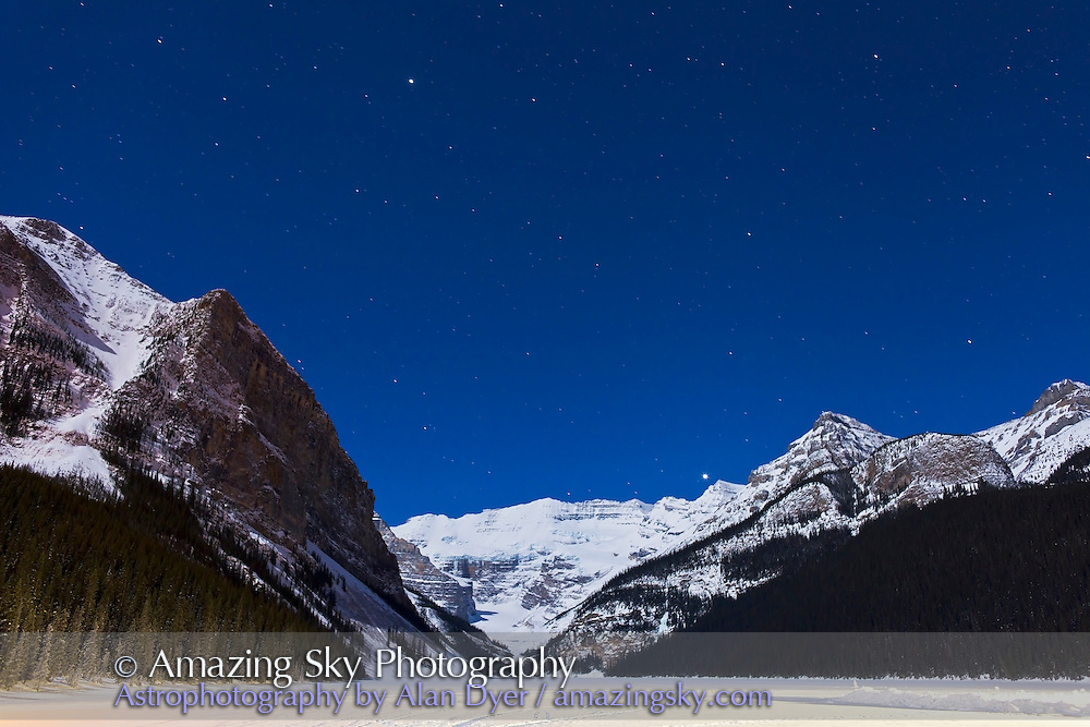 Lake Louise under light of gibbous Moon on February 4, 2012, on a very clear night in Banff. This was taken from the shore of the frozen lake. It is a 30-second exposure at f/3.5 and ISO 400 with the Canon 5D MkII and Canon L-series 24mm lens. Venus is the bright object just about to set behind Mount Victoria, Jupiter is the bright object at upper left. Fairview Mountain is at left.
