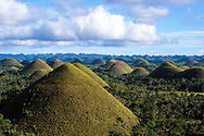 The Chocolate Hills is an unusual geological formation in Bohol, Philippines  According to the latest  survey done a few years back, there are 1,776 hills spread over an area of more than 50 square kilometres or 20 square miles. They are covered in grass that turns brown during the dry season, hence the name. The Chocolate Hills are featured in the provincial flag and seal to symbolize the abundance of natural attraction in the province
