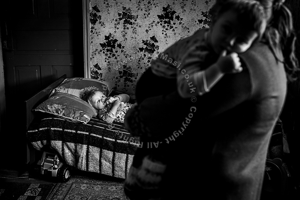 Julia Mosiyenko, 32, is holding one of her twin sons, Ilya and Rodion, 2, while the other is laying on a bed inside a house in the town of Gorska, near the frontline in eastern Ukraine, where they took refuge after their own home was damaged beyond repair during shelling in January 2015.