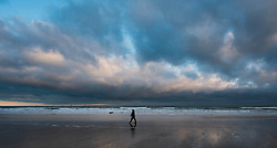 © Licensed to London News Pictures. 10/03/2014<br /> <br /> Saltburn, Cleveland, United Kingdom<br /> <br /> A woman walks her dog along the beach at first light in Saltburn by the Sea in Cleveland as large cloud formations are seen far out to sea.<br /> <br /> Photo credit : Ian Forsyth/LNP