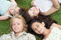 Smiling Pre-teen Children Lying on backs in circle on Grass overhead view