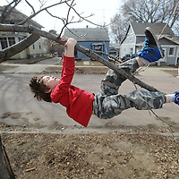 Gage Lantgen, 6, hangs from a tree branch in his front yard off of West Avenue near Sanford Hospital while enjoying the warm weather on Wednesday, April 9, 2014.<br /> (Jay Pickthorn/Argus Leader)