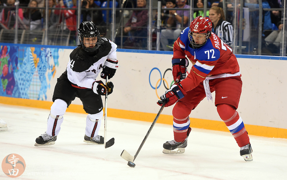 Feb 16, 2014; Sochi, RUSSIA; Russia forward Yekaterina Pashkevich (72) battles for the puck with Japan defenseman Ayaka Toko (4) in a women's ice hockey classifications round game during the Sochi 2014 Olympic Winter Games at Shayba Arena.