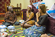 VSO ICS volunteers Francisca Mlingwa and Josie Kearney sitting down to an evening meal with Mr Abdul Issa Makolela in their host home. Volunteers stay with local families get the full experience. Lindi, Lindi region. Tanzania.