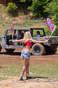 A young woman raises confederate flags to start a truck pull competition during the 2015 National Red Neck Championships May 2, 2015 in Augusta, Georgia. Hundreds of people joined in a day of country sport and activities.