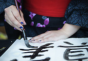 """A volunteer writes the kanji for """"Truth"""" on a paper lantern during the annual From Hiroshima to Hope event at Seattle's Green Lake. The year 2015 marked the 70th anniversary of the bombings of Hiroshima and Nagasaki. (Lindsey Wasson/The Seattle Times)"""