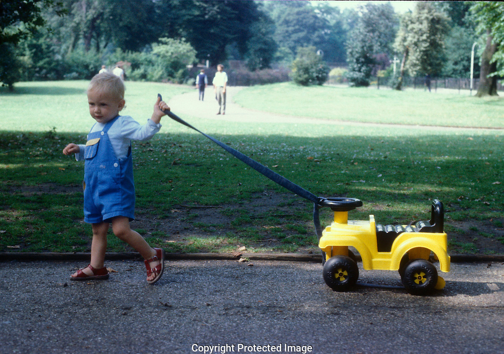 Toddler pulling toy car in Battersea Park, South London