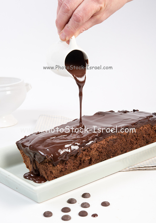 Pouring chocolate sauce over a chocolate freshly baked cake