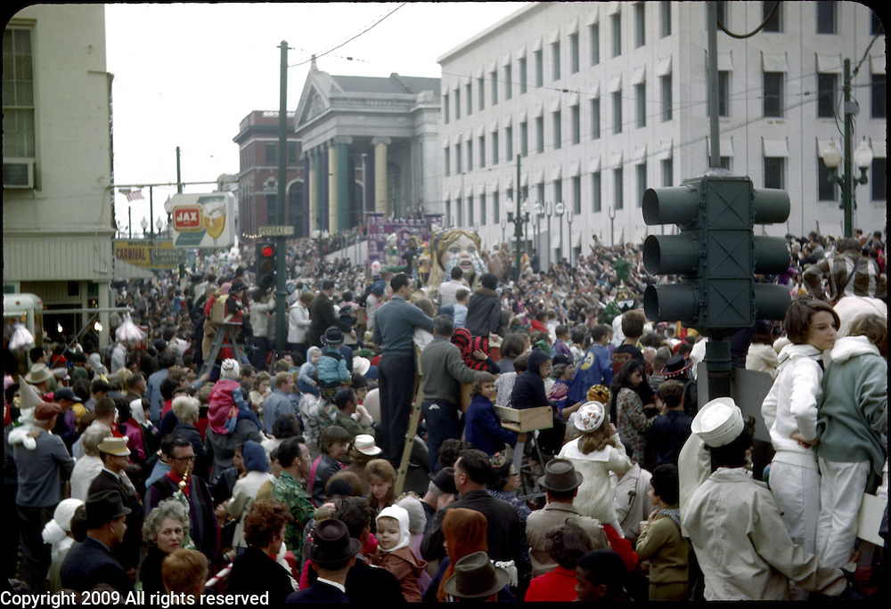 Revelers participate in the 1966 Mardi Gras parade in New Orleans, Louisiana. A crowd of arade goers watch from a street corner.