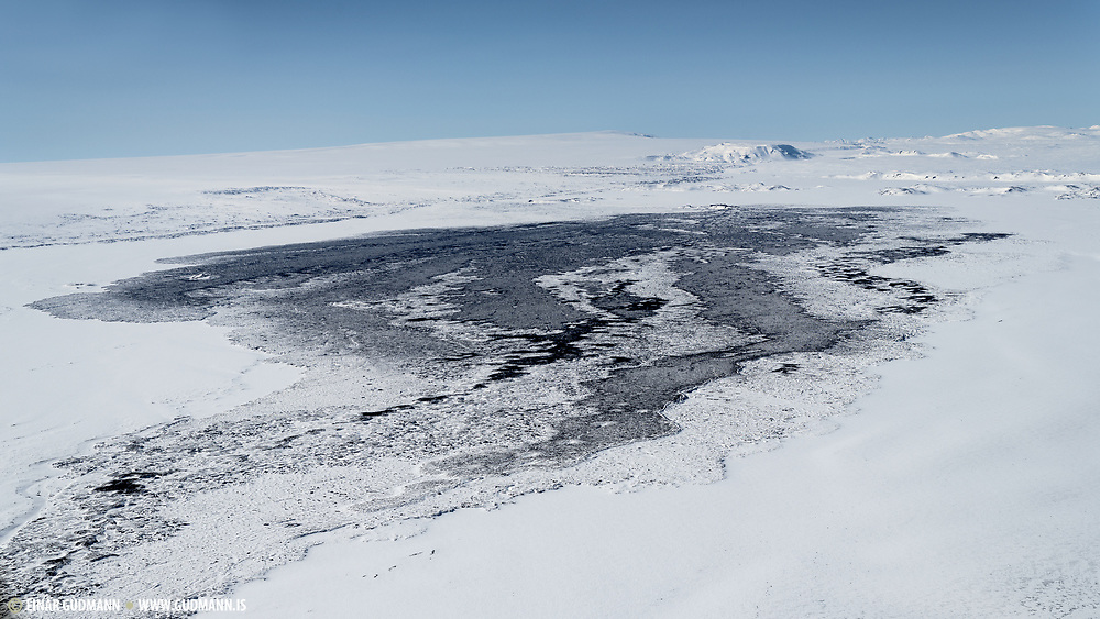 The Holuhraun crater is in the distance. The lava stream is still black and warm in the wintertime. Taken 2018.