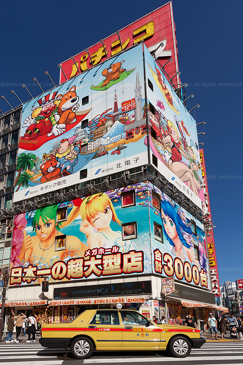 A taxi at a crossing in front of a large colourful display for a Pachiinko Parlour in Shinjuku, Tokyo, Japan. Friday September 28th 2018