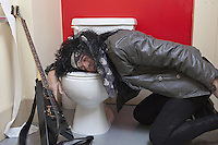 Exhausted senior male guitarist sleeping in toilet