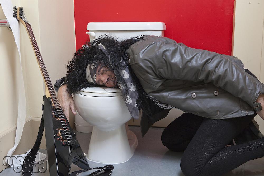 Exhausted senior male guitarist sleeping in toilet