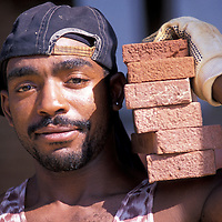 Bricklayer Nathaniel Sim carries bricks at the Quaker Hill development in Alexandria, Virginia. Release available.
