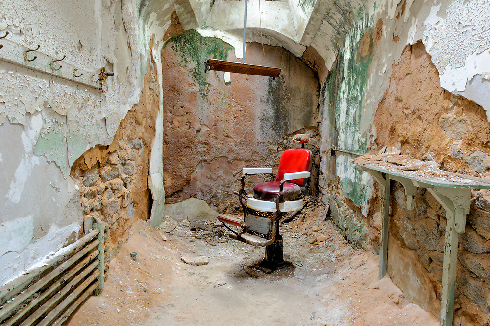 These are the remains of a barber shop in one of the most notorious and haunted prisons in history, the Eastern State Penitentiary in Philadelphia. This is a typical cell in the prison, narrow with stone walls parged with cement, a barrel roof with a single central skylight, and just bare pipes for a radiator. Over the years, the place was left to crumble and today it is considered a stabilized ruin, meaning the only repairs done are to keep it from falling down even further.<br />
