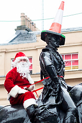 Dressed as Santa Claus, Ricky McConnell sits behind the Duke of Wellington on the statue in Royal Exchange Square Glasgow<br />