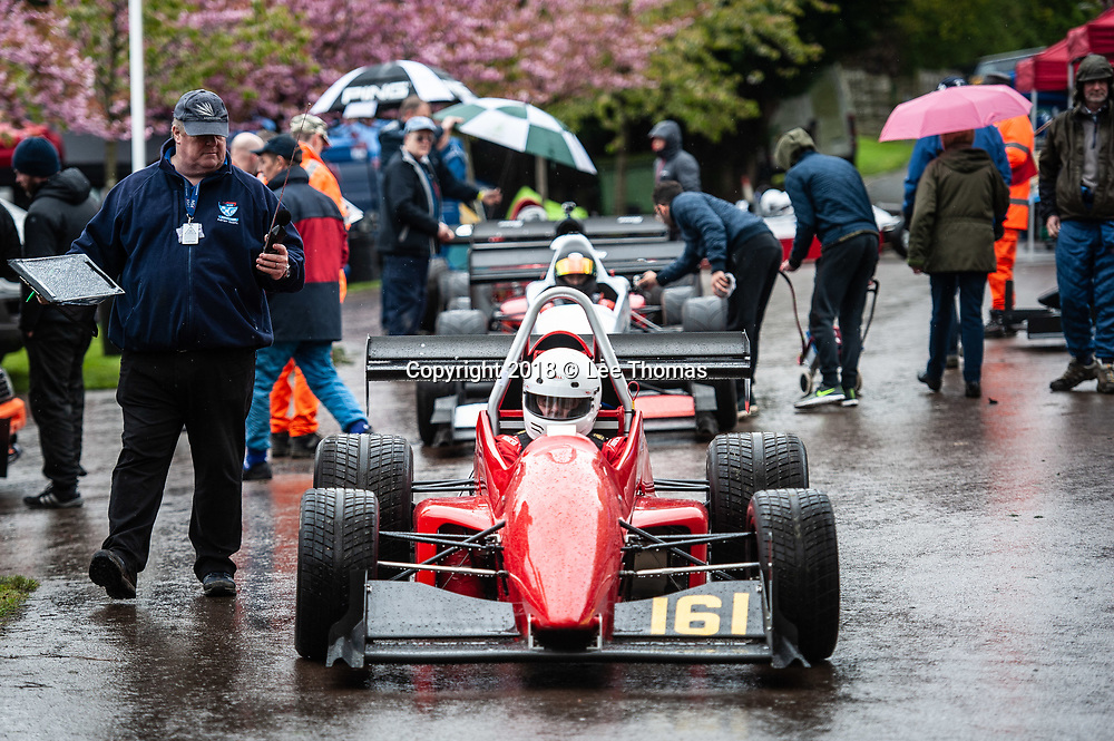 Prescott Hill, Gotherington, Cheltenham, Gloucestershire, UK. 28th April 2018.  Pictured:  Competitors line up their racing cars in the Paddock area to await their turn to speed up a very wet Prescott Hill track. /  Some of the fastest hillclimb cars in the country braved April showers to  compete in the opening round of the UK's premier championships at the historic Prescott Hill in Gloucestershire, home of the UK's Bugatti Owners' Club.  The two day event features the opening rounds of the British & Midland Hillclimb Championships as well as rounds for the Bugatti Owners' Club (BOC) New Barn Roadgoing and the Aldon Classic Championships. The weekend meeting also entertained hundreds of spectators with an appearance from the National Hill Climb Association (NHCA) motorcycles, several with attached sidecars.  //Lee Thomas, Tel. 07784142973. Email: leepthomas@gmail.com  www.leept.co.uk (0000635435)