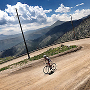 A lone cyclist ascends the dirt road of Sunshine Canyon, above Boulder, Colorado.