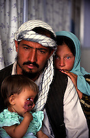 KABUL 06 August 2005..MAIWAND HOSPITAL..Shabana sister sits behind her father in the pre-registration room. ....Shabana, a nine-months old Afghan girl, was originally diagnosed with 'Leishmaniasis' a parasitic disease spread by the bite of infected sand flies; then with 'Hemangioma' a tumor made-up of dilated blood vessels that usually appears shortly after birth; and finally with 'Neurofibroma'  a tumor or growth located along a nerve or nervous tissue