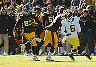 November 23 2013: Iowa Hawkeyes wide receiver Jordan Cotton (23) returns a kick as Michigan Wolverines defensive back Raymon Taylor (6) cuts back during the second quarter of the NCAA football game between the Michigan Wolverines and the Iowa Hawkeyes at Kinnick Stadium in Iowa City, Iowa on November 23, 2013. Iowa defeated Michigan 24-21.