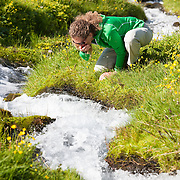 Anna Dóra Hermannsdóttir drinking from a small stream while hiking at Klængshóll travel farm, Skíðadalur, North Iceland.
