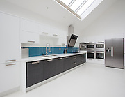 large open white kitchen with units, fridge freezer and roof lights