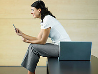 Office worker sitting by laptop sending text message