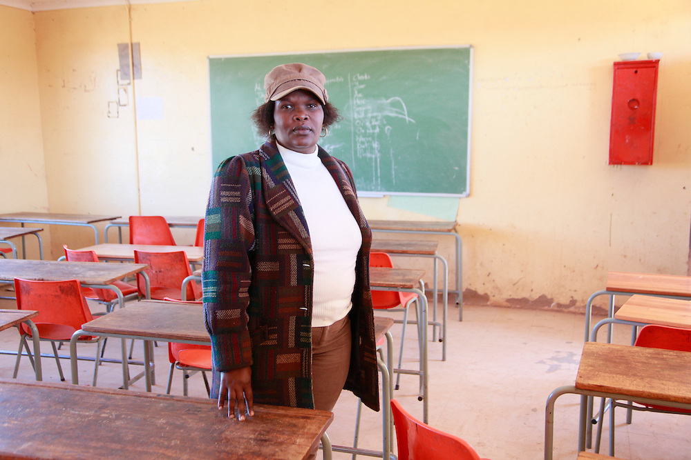 Gladys Mangope teacher at Kgalatlowe High School. The school has no money for maintenance, its a science school but has no laboratories and only 14 computers for it's 293 students.<br /> <br /> Mothlabe is a small community in the midst of the Platinum belt North of Rustenburg. During the apartheid era they were forced under the rule of a neighbouring Traditional Authority and the village boundaries redrawn.  In the late 1990&rsquo;s they submitted a claim for land restitution but the claim came back as a failure but no reasons where given. They have since appealed but heard nothing. In 2004, a platinum mine began operating on the land in question and it&rsquo;s profits have been used to develop other villages. When the Mothclabe community proposed independence by forming their own Traditional Authority they were issued with a court interdict preventing them from holding meetings and using the term &lsquo;Mothlabe Traditional Authority.&rsquo;  The Legal Resources Centre has since successfully defended them in court against the interdict. Meanwhile Mothlabe remains poor and restitution of their land is no closer.  <br /> <br /> Mothlabe, North West Province, South Africa. 2011<br /> <br /> &copy;Zute &amp; Demelza Lightfoot / Legal Resources Centre
