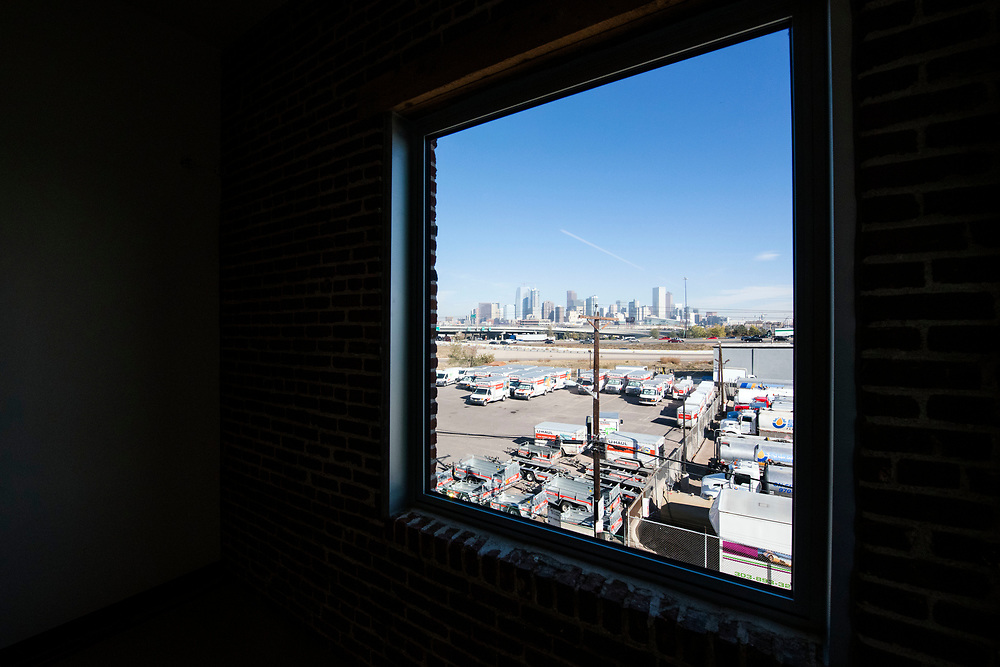 DENVER – NOV. 3. The Denver skyline is pictured from a community yoga room window inside STEAM on the Platte, a new and historic reuse space recently developed at 14th and Zuni streets in Denver's Sun Valley neighborhood. (Photo by Andy Colwell/Special to The Denver Post)