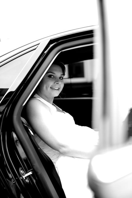 Der Chauffeur der Braut ist angekommen und sie ist in das Auto eingestiegen und freut sich auf die Fahrt zur Kirche.