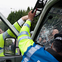 LONDON, ENGLAND - SEPTEMBER 11:  Police officers  check the damage to the van windscreen after stones were thrown at them during clashes in front of Harrow Central Mosque on September 11, 2009 in London, England.  (Photo by Marco Secchi/Getty Images)