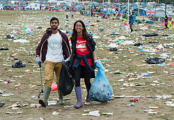 © Licensed to London News Pictures. 29/06/2015. Pilton, UK. The Glastonbury Festival cleanup operation.  Teams of over 350 people collect the rubbish from the Pyramid Stage site, consisting of food, cups discarded collapsable chairs, bottles of urine and other detritus, bag it to be loaded into collection lorries.  The cleanup operation is in progress everywhere throughout the site to restore it to pristine order.  Photo credit: Richard Isaac/LNP