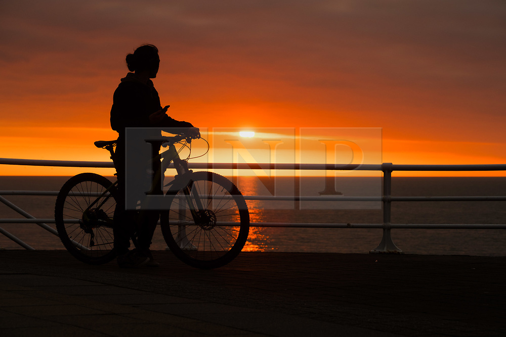 © Licensed to London News Pictures.<br /> Aberystwyth UK, 26/03/2019 A beautiful sunset , at the end of another day of warm spring sunshine, silhouettes  a man on his bicycle on the promenade  in Aberystwyth, on the Cardigan Bay coast of west Wales. High pressure continues to dominate the weather for much of the UK, with settled conditions and clear blue skies<br /> photo Keith Morris/LNP