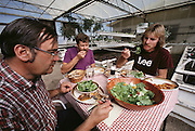 USA_SCI_BIOSPH_71_xs <br /> Biosphere 2 Project environmental research lab. Eating lunch of tilapia fish harvested from the Bioshphere 2 rice fields during a test phase prior to the sealing of the Biosphere.  Biosphere 2 was a privately funded experiment, designed to investigate the way in which humans interact with a small self-sufficient ecological environment, and to look at possibilities for future planetary colonization. The $30 million Biosphere covers 2.5 acres near Tucson, Arizona, and was entirely self- contained. The eight 'Biospherian's' shared their air- and water-tight world with 3,800 species of plant and animal life. The project had problems with oxygen levels and food supply, and has been criticized over its scientific validity. 1987