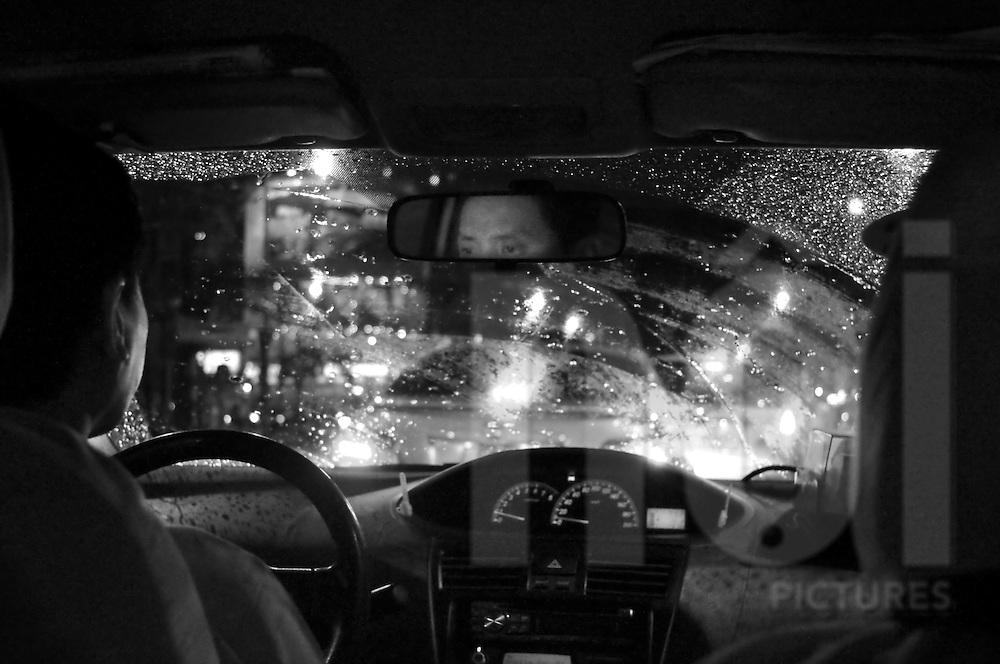 Interior of a taxi car by night on a rainy day. Ho Chi Minh city, Vietnam, Asia