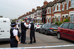 © Licensed to London News Pictures. 16/04/2020. London, UK. Police officers stand on Alric Avenue outside a house with a burnt facade. The Metropolitan Police Service were called at 02:15BST to a residential address in Alric Avenue NW10 following reports of a fire. Police officers attended with the London Fire Brigade (LFB) and London Ambulance Service (LAS). A 36-year-old woman was taken to hospital with serious injuries. She was pronounced dead at 06:07BST. Another woman, aged in her 60s, was also taken to hospital and treated for non life-threatening injuries. A man in his 40s was arrested on suspicion of arson and taken into police custody. Photo credit: Peter Manning/LNP