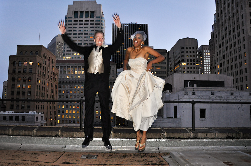 "Noam & Uzoezi do the ""just married jump"" on the roof of the Merchant's Exchange, San Francisco"